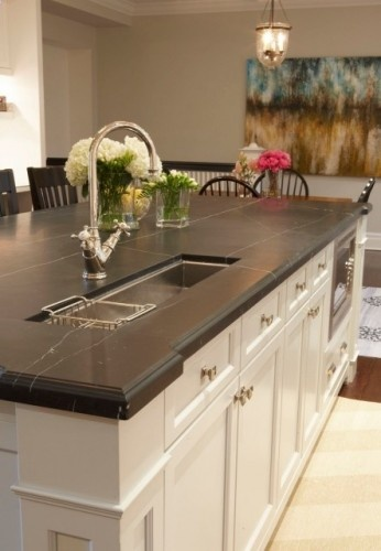 Soapstone counter island with small trough sink and white cabinets