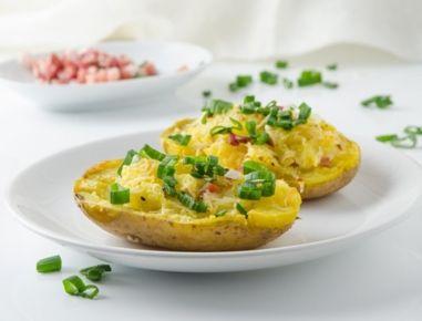 Für die Potato Skins zunächst die Erdäpfeln mit der Schale in Salzwasser kochen, bis sie weichsind. Ein wenig auskühlen lassen und dann der Länge