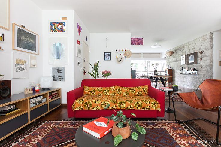 Sala de estar com pegada étnica tem sofá vermelho tecido estampado por cima, tapete kilim e poltrona Paulistano.