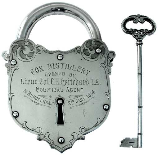 silver padlock and key with engraved foliate decoration commemorating the opening of the 'Cox Distillery' in Bundelkand, 2nd Jany 1914, marked JCBS & Co, Bechtler, Allahabad, 6.25in overall height,