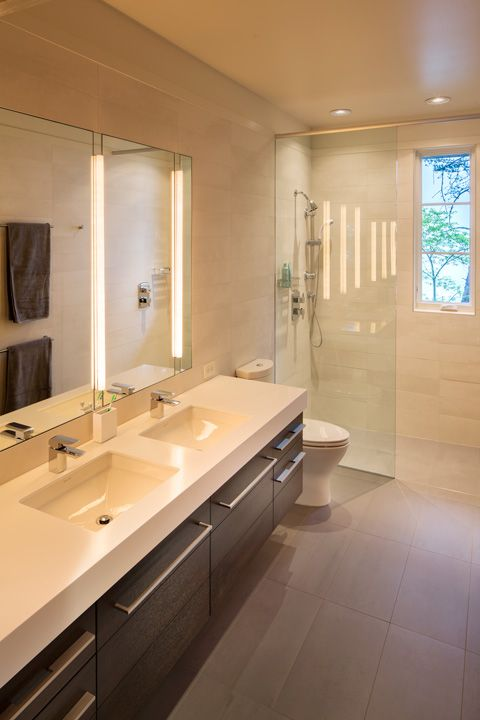 Modern white bathroom with large curbless shower. His and her sinks and modern, sleek drawer pulls and white horizontal tile.
