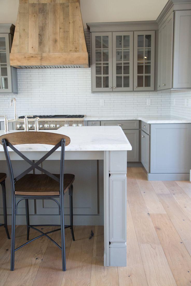 grey farmhouse kitchen . custom barnwood hood. open concept