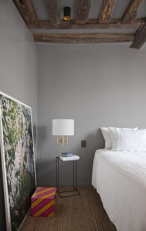 Sotto i tetti di Parigi LA CAMERA DA LETTO PADRONALE Con le pareti dipinte in un caldo tono di grigio e il soffitto segnato dalle travi originali di legno. Il pavimento è quasi interamente coperto dal tappeto-stuoia.