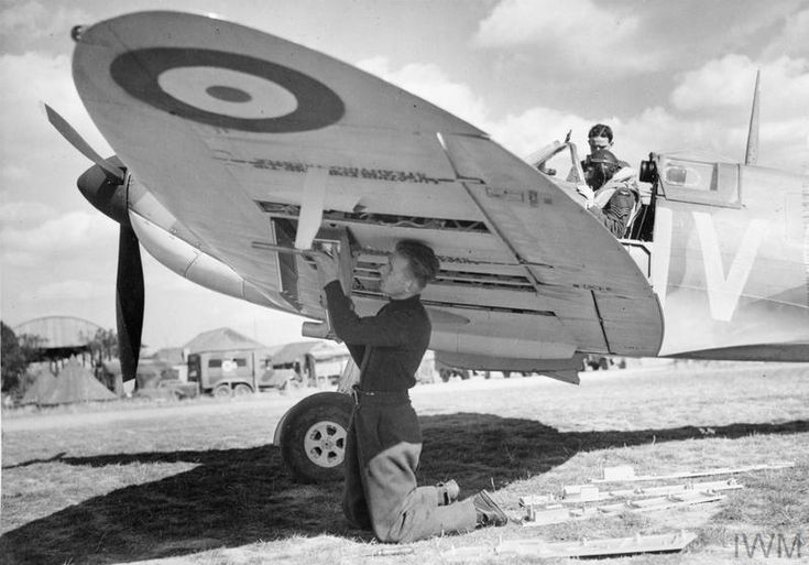 Armourer Fred Roberts re-arms Supermarine Spitfire Mark IA, X4474 'QV-I', of No. 19 Squadron RAF at Fowlmere, Cambridgeshire, while the pilot, Sergeant B J Jennings, has a word with his mechanic. Manor Farm can be seen in the background.