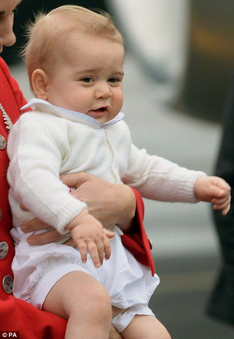 Full of energy: Held securely in his mother's arms, Prince George seemed unfazed by their 30-hour flight and squirming about looking eager t...