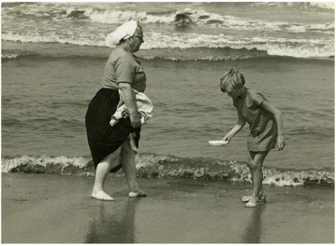 Strand, Scheveningse vrouw in dracht, pootje badend in zee. 1968 N. de Lange #ZuidHolland #Scheveningen