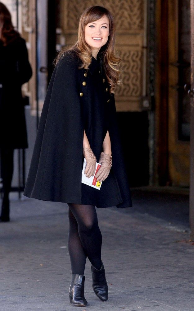 Olivia Wilde was a classic beauty on the set of her new flick wearing a chic navy cape with brass buttons.