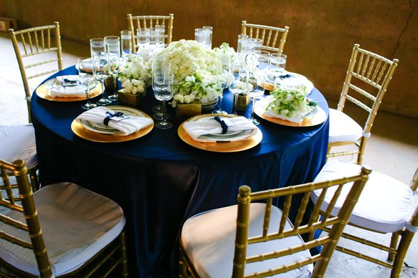Navy Satin Linen With Gold Chargers And Ivory Flower