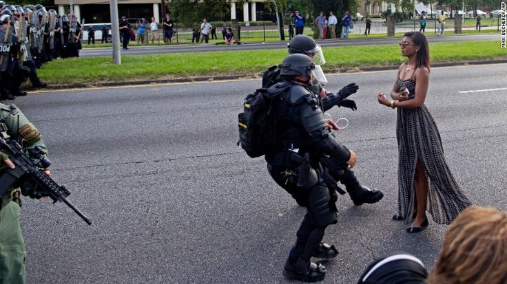 A protester is grabbed by police officers in riot gear after she refused to leave the motor way in front of the the Baton Rouge Police Department Headquarters in Baton Rouge, Louisiana, on Saturday.