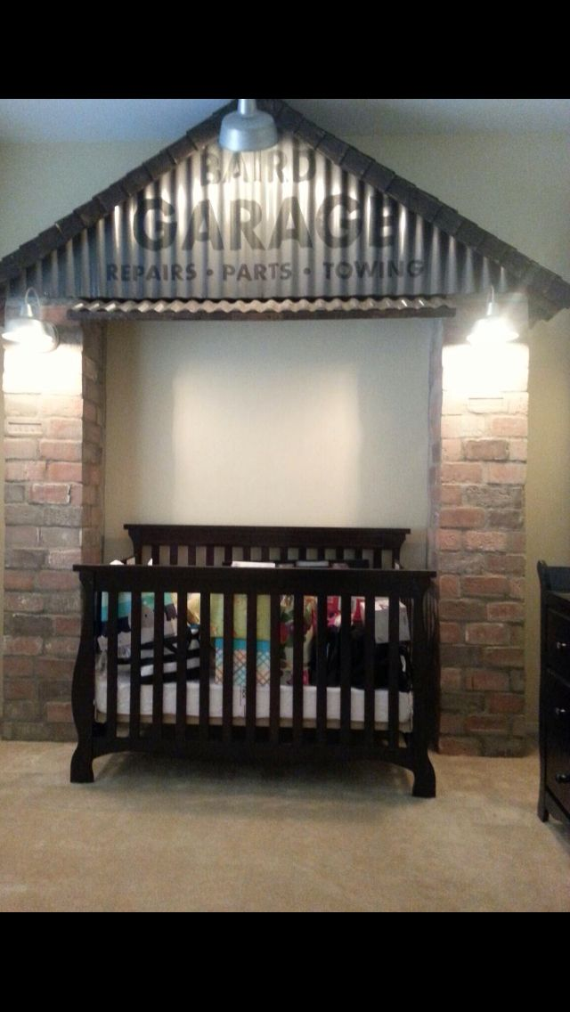 Creative idea for a vintage car room with a custom garage theme wall around the crib or bed.