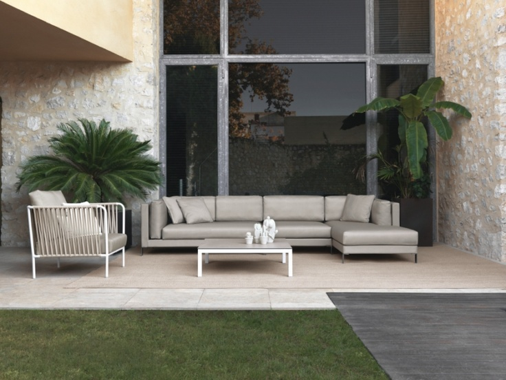 Slim modular composition in Taupe Silvertex pairing with a Nido armchair, a coffee table with a porcelain tabletop and a great outdoor rug made of polyester rope designed to be extremely durable.
