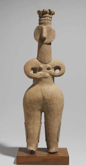 Iranian terracotta female figure, 1st milelnium B.C. With exaggeratedly broad hips and buttocks, and thick tapering legs, her pubic triangle slightly raised, with round sloping shoulders and curving arms, her hands resting on her abdomen below her small conical breasts, the heart-shaped face high on her columnar neck, with a pronounced nose, the eyes formed of incised concentric circles, her ears with multiple perforations, wearing a three-tiered crown, 50 cm high. Private collection