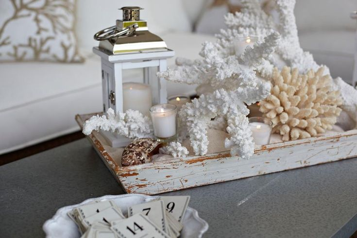 1. Fill a tray with sand (hint: if you don't live near the ocean use our sand vase filler!)  2. Place seaside objects such as faux coral and seashells on sand as desired.  3. Add in a lantern and candles for a little extra ambience.
