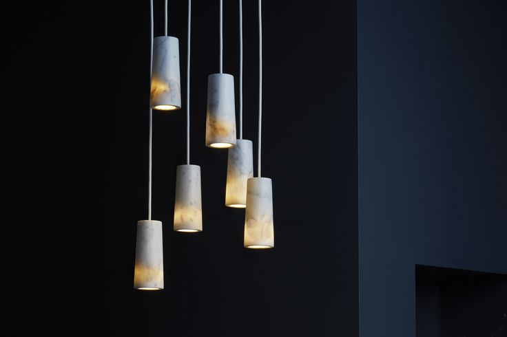 Core cluster of six pendants in Carrara marble. A warm glow is created around the base of each pendant when lit.