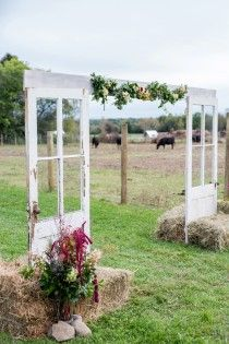 Contemporary ceremony arch with repurposed doors and hay bales