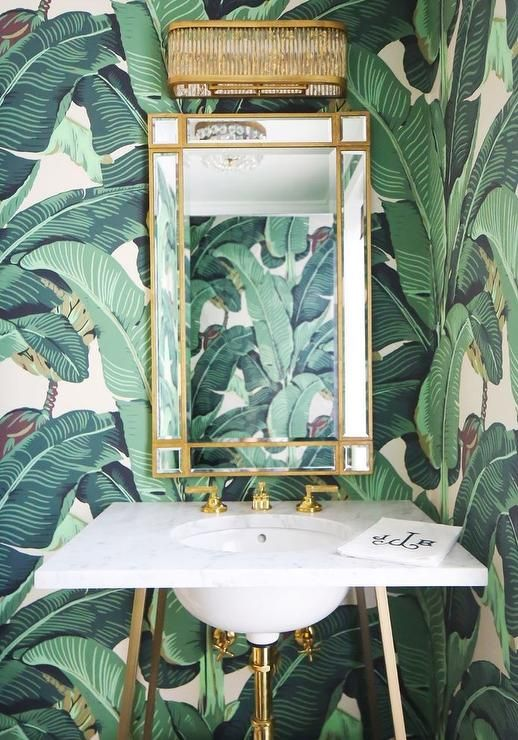 Martinique Banana Leaf Wallpaper makes this gorgeous powder room stand out and beautifully complements a brass trim mirror mounted beneath a brass and glass sconce and above a marble and brass washstand finished with a round sink and polished brass faucet kit.