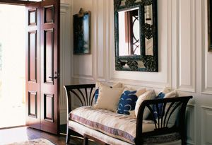 This entrance hall incorporates an Italian daybed, a Dutch mirror, a Persian rug and a Venetian chandelier, all from different time periods.