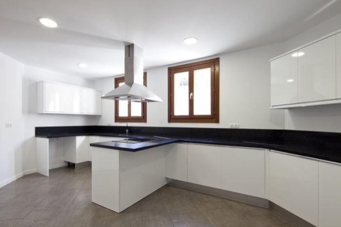 Cocina en blanco y negro con toques de madera. Da sensación de limpieza.