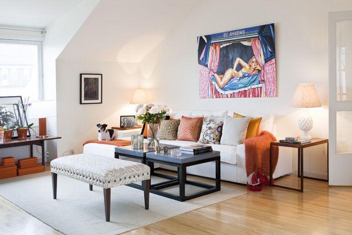Vardagsrummet ljust och luftigt med inslag av orange. Soffa från Ikea, plädar Kamelo. Ullmatta från R.o.o.m., sidoborden i jakaranda är ett fynd från ett dödsbo.
