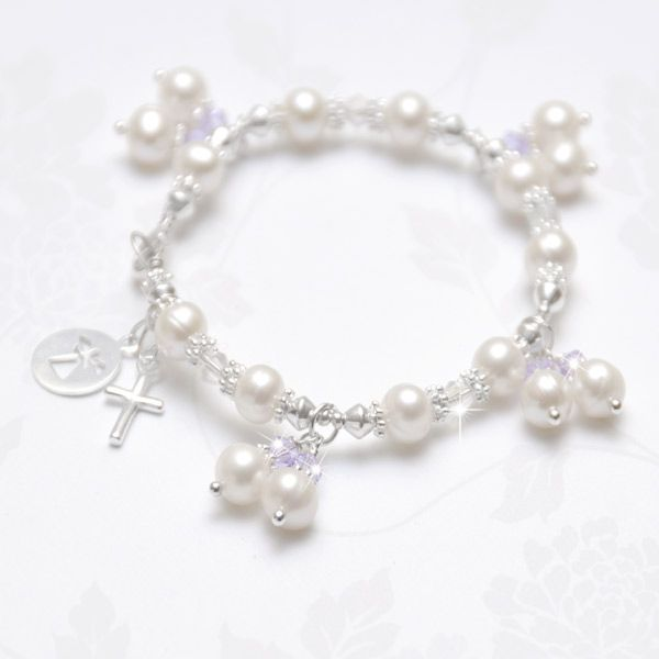 Heavenly Angel Freshwater Pearl Bracelet - This intricately designed bracelet is sure to capture the heart of your little one. A row of lustrous ivory freshwater pearls (5-6mm), a scattering of 4mm Swarovski crystals and bright sterling silver beads make for an enchanting design. Accented with graceful pearl and lavender crystal drops add a splash of fun to this darling design. Embellished with a 15mm sterling silver cross an a 12mm sterling silver angel disc charm.
