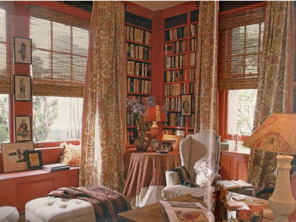 2113  House Beautiful: Decorating with Books; Hueston    This red library with bookcases around at least two walls has an English Country feel about it. The floral-print draperies, the antique table, the window seat, the small art prints and personal photographs interspersed with the books – all make this an inviting space.: House Beautiful, 2113 House, Antique Tables, English Country, Photographs Interspersed, Country Feel