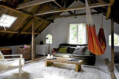 An attic getaway - rustic bohemian living space. Love the exposed timber beams, fur rug and hammock!
