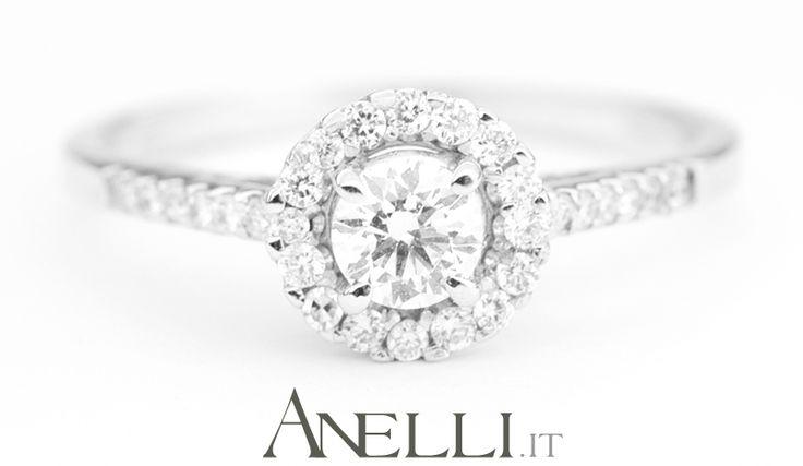 Un delizioso Anello da Fidanzamento caratterizzato da un solitario centrale e una corona di diamanti laterali..