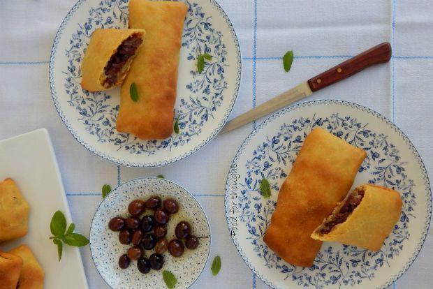 Δεν ξέρω τι μου αρέσει περισσότερο σε αυτές τις πίτες. Η γλυκιά, λαδένια ζύμη τους ή η πικάντικη γέμιση με την αψάδα της αλμυρής ελιάς, που την καταπραΰνει το σχεδόν μελωμένο κρεμμύδι;