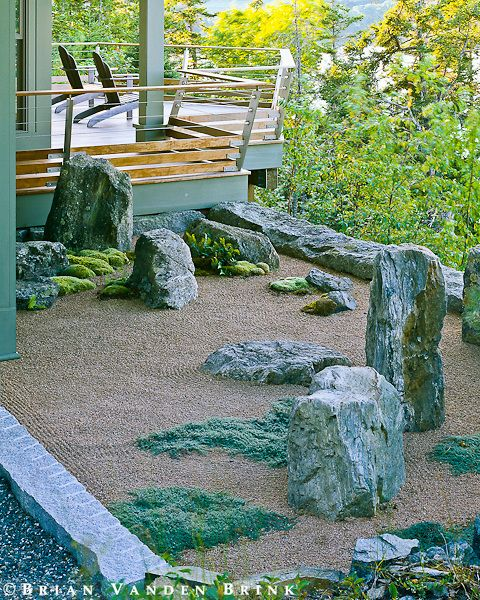 a stone garden of a house in coastal maine