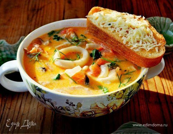 Сливочный суп с морепродуктами, томатами и пармезановыми гренками. Ингредиенты: морской коктейль замороженный, лук репчатый, чеснок