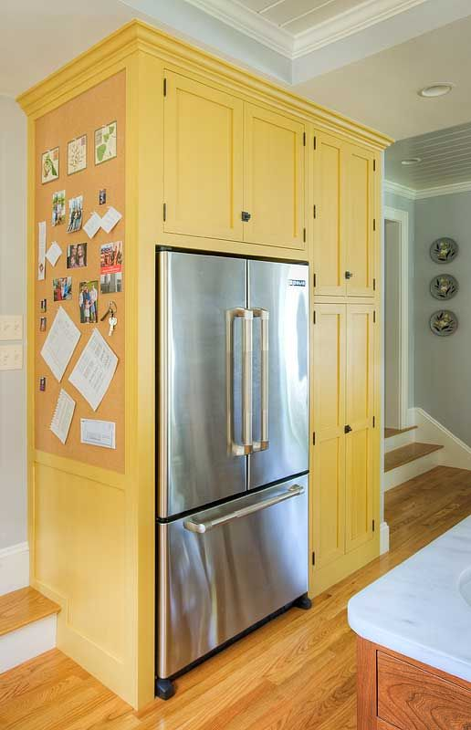 Probably not the Yellow kitchen cabinets - but i like the cork bulletin board on end panel of refrigerator surround