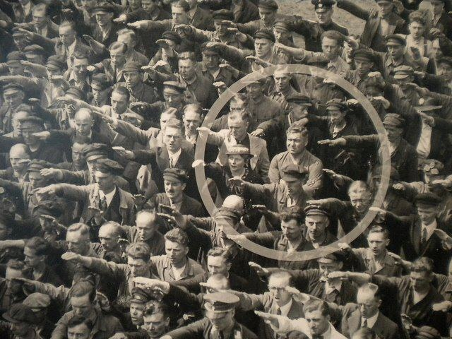 The man with his arms crossed, refusing to salute the ship, is August Landmesser, a shipyard worker who had been persecuted for having a relationship with a Jewish woman. Amid all those cheering and saluting the warship, August Landmesser courageously refused.