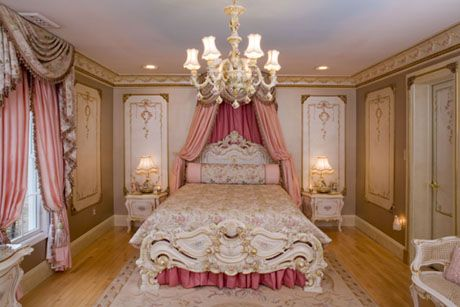 this bedroom has a Renaissance influence. With the gold and the chandelier along with the bed canopy and the rich looking fabric.