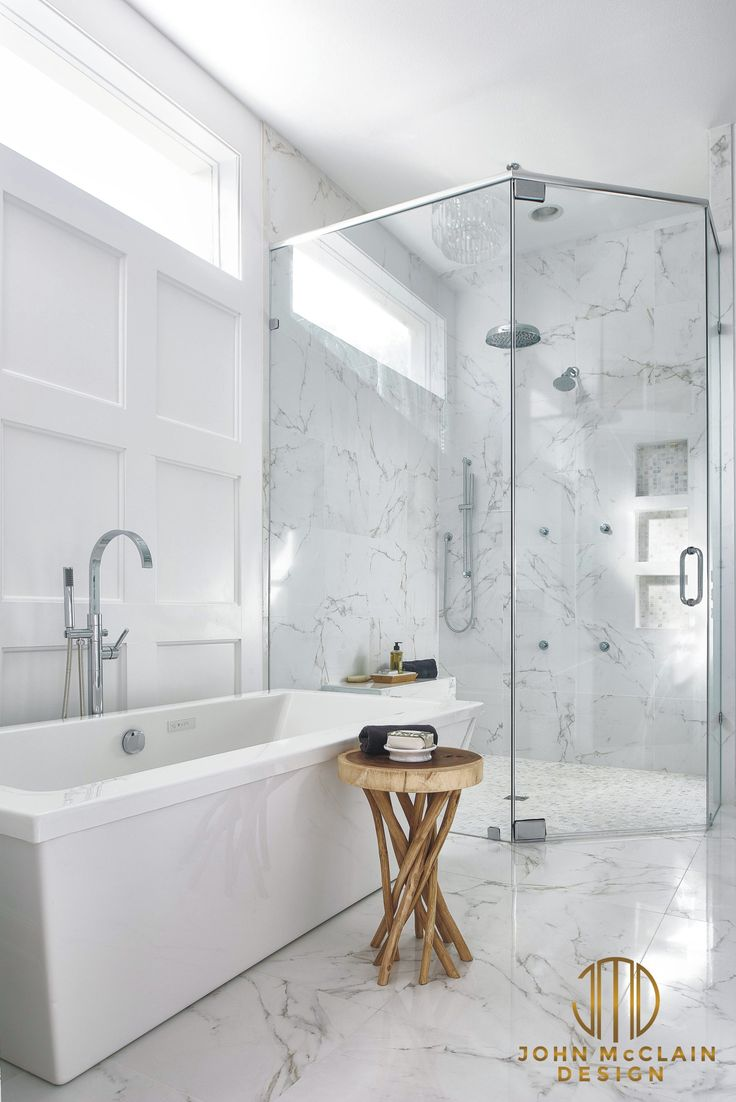 This bathroom renovation included a larger corner, curbless shower, freestanding air tub and custom paneled walls. High quality porcelain tiles have a realistic carrara marble look while offering the durability of porcelain. The shower has wall jets, rain head, wall shower head and handheld wand. Stephen Allen Photography