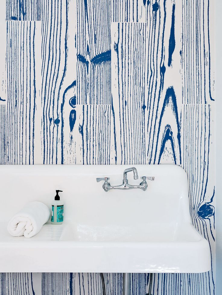 White & blue, wood grain patterned UonUon tiles by 14 oraitaliana line the bathroom walls