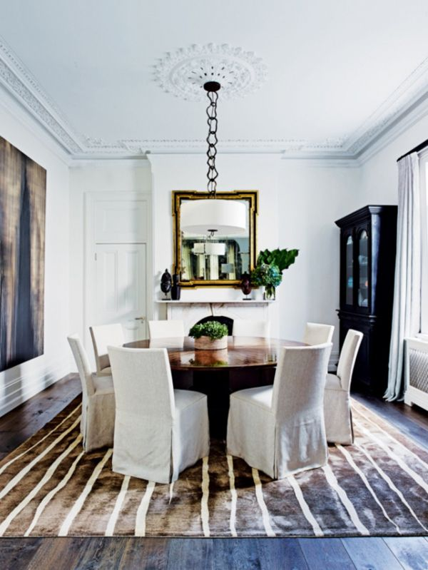 round table formal dining room with slipcovered chairs and striped rug