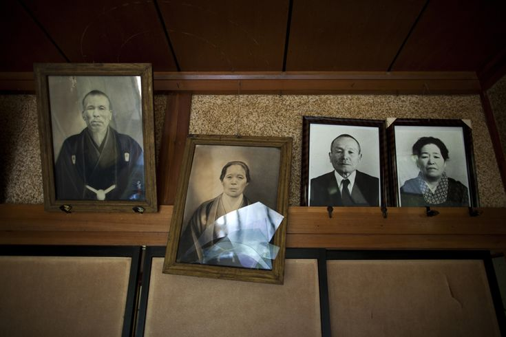 A portrait of a family member, dislodged and shattered by the March 11 earthquake, hangs on the wall of an abandoned farmhouse in Naraha, Japan within the exclusion zone.