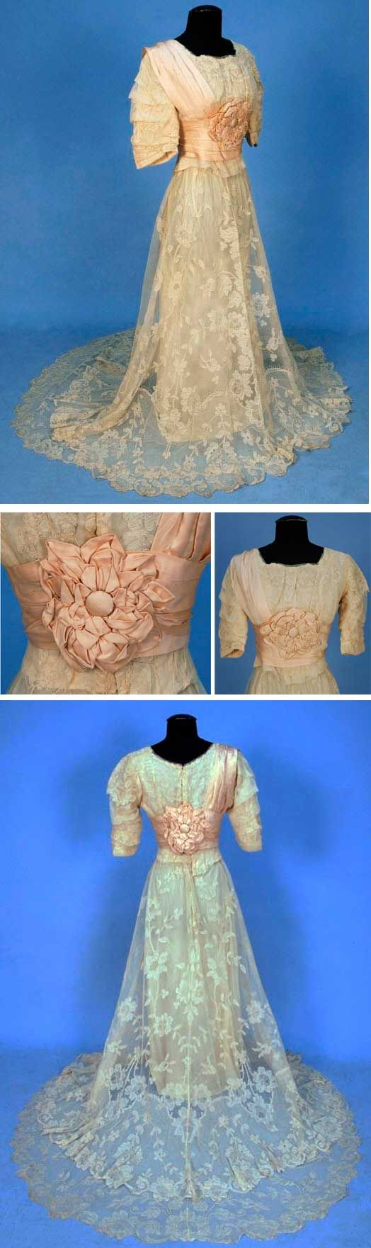Trained lace gown, ca. 1906. Two-piece re-embroidered lace on net. Boned bodice with pleated short sleeves. Pink silk cummerbund with self flower and shoulder drape. Skirt has deep hem ruffle to train, non-conforming silk under-dress. Charles A. Whitaker Auctions/LiveAuctioneers