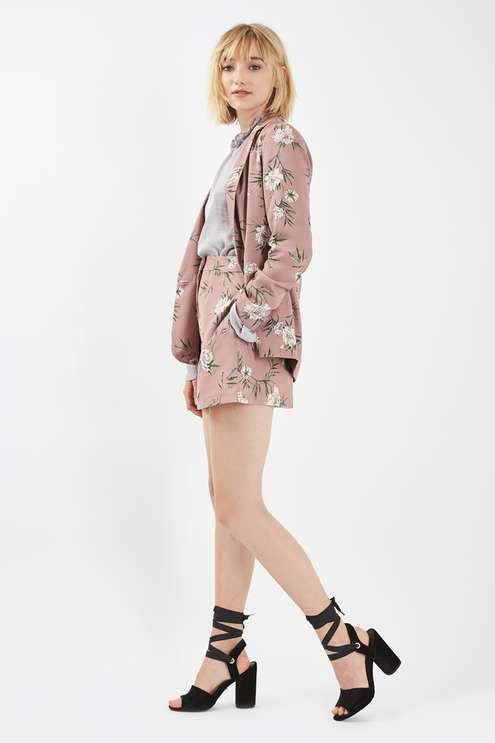 A smart style gets a girlie update in this floral print blazer in mauve. A one-of-a-kind piece, it comes with shorter length sleeves, a structured collar, covered buttons and a contrast lining to the interior. Style with matching shorts for a co-ordinated cool feel. #Topshop