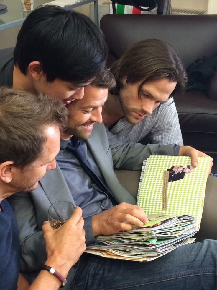 SPN boys with a scrapbook made for them. Misha looks so happy with all his men draped over him.