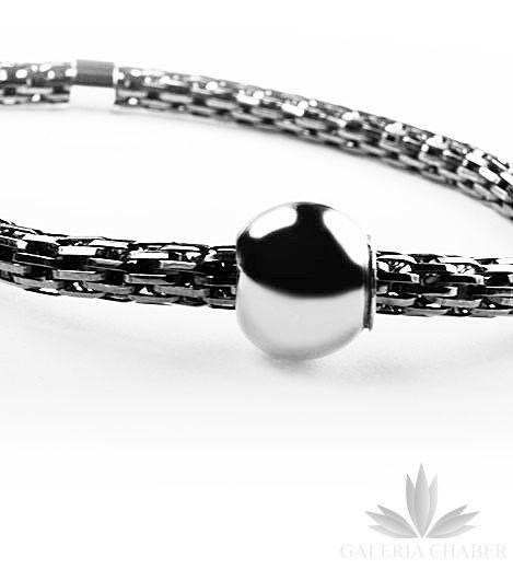 Bransoletka wykonana ze srebra próby 925. Bransoletka regulowana, w środku umieszczono silikonową gumkę przez co dopasowuje się ona do grubości nadgarstka. Wzór ciekawy, pleciony ozdobiony gładką kulką wykonaną również ze srebra w kolorze ciemnym - oksydowana. Szczególnie polecamy z innymi bransoletkami w zestawie - istnieje także inna wersja kolorystyczna ciemne srebro z kulką w kolorze złotym. Średnica kulki to około 1 cm.