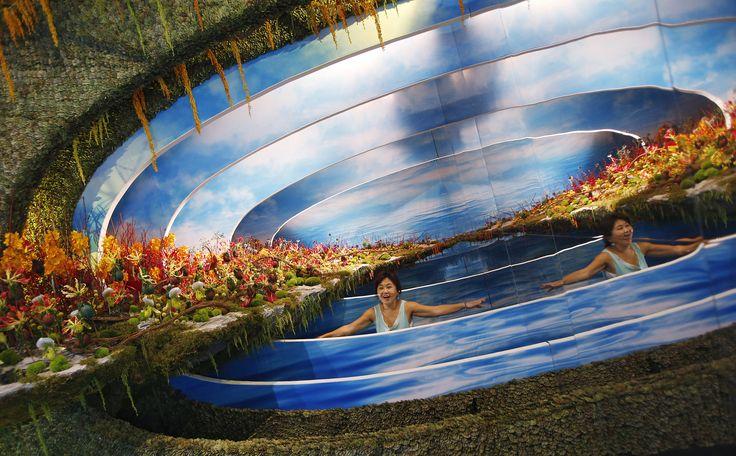 """Kathy Ong dari Malaysia berpose untuk foto di depan tampilan kreasi bunganya """"Refleksi Musim Gugur"""", yang dipamerkan pada Festival Taman di Singapura yang berlangsung pada tanggal 16 - 24 Agustus di Singapura."""
