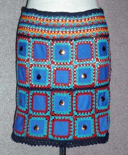 Falda tejida a crochet en hilos de colores rojo, turquesa, anaranjado, negro y azul con aplicaciones en modal azul, adornada con lentejuelas, Talla M