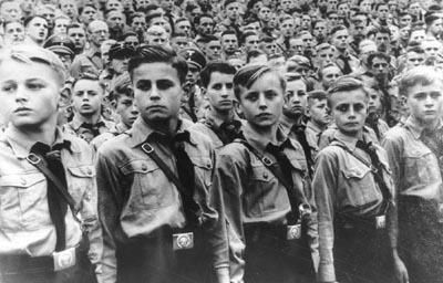 "Grim beyond their years, boys belonging to the Hitlerjugend (Hitler Youth) turn eyes at a Nazi rally. Their belt buckles carry the stern motto: ""Blood and Honor"".  The Hitlerjugend admitted children at the age of 10, and continued until the age of 18. It was organized on a military pattern and prepared a young man to become a soldier or an SS. The young men were indoctrinated with the Nazi ideology."