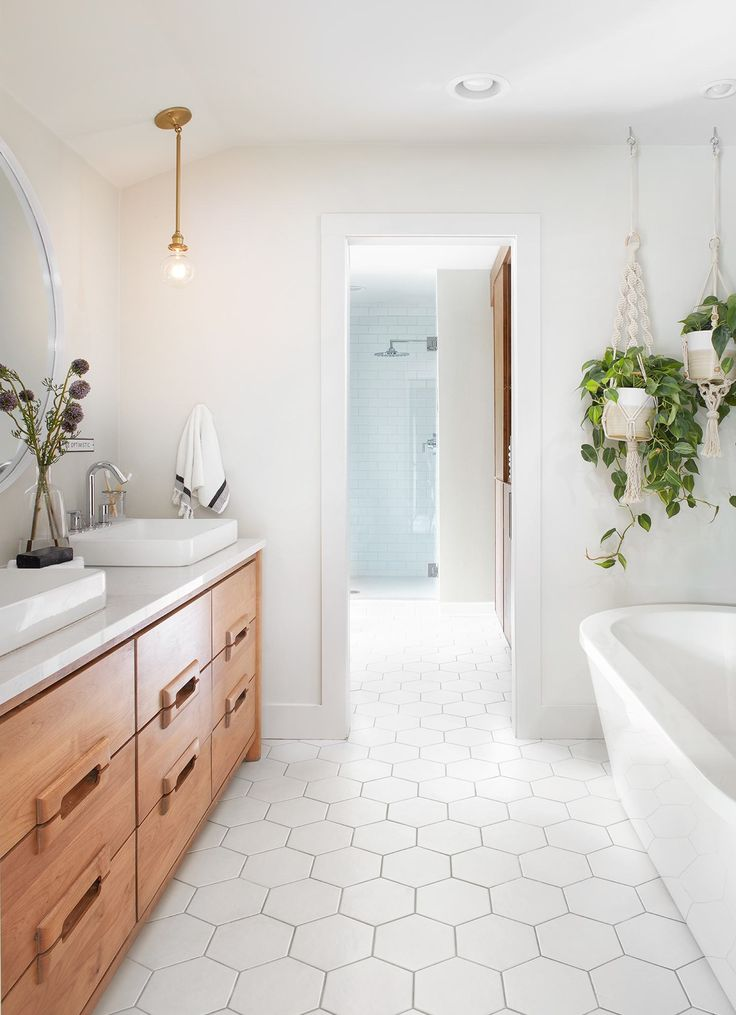 The master bath has one of the most interesting vanities of the season. I love its drawer pulls—they feel like a nod to the the mid century modern style. This whole space feels really clean. The shape from the hexagon tile and the green of the hanging plants creates a lot of cool texture.