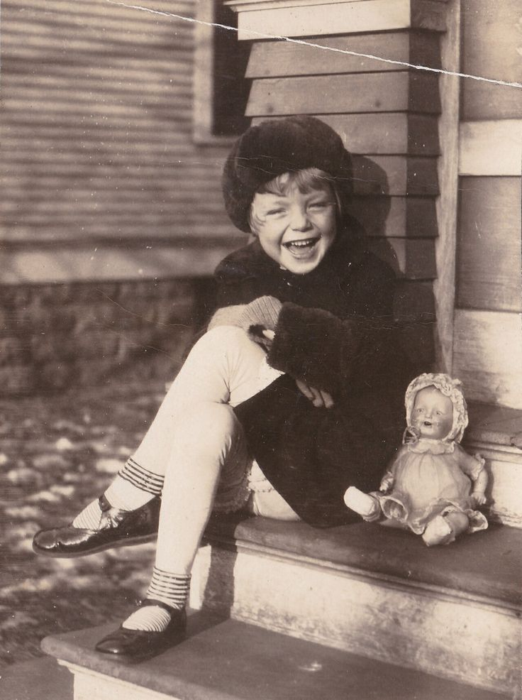 Young girl, circa 1920, sitting on porch steps with her doll
