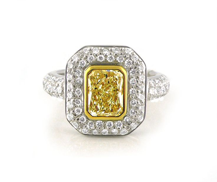 An 18ct White and Yellow Gold, Fancy Yellow Radiant Cut Diamond Halo Ring