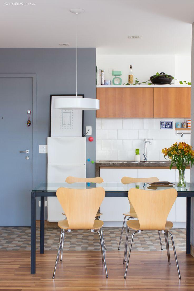 Sala de jantar integrada à cozinha tem mesa de vidro e cadeiras series 7.