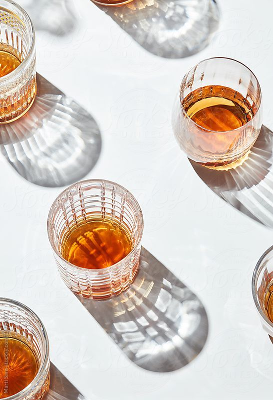 Top view of glasses of whiskey or scotch on white background. by Martí Sans for Stocksy United