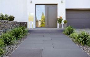 Wie ein roter Teppich wirkt der Zuweg durch große Steinplatten. Gesäumt von Gräsern, die im Schotter vom Wind hin und her wiegen. Über das farblich passende Podest gelangt der Besucher zu dem modernen Entree des Hauses. Schnörkellos. Gerade. Im perfekten Design.